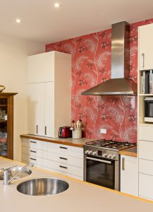 The new kitchen with high gloss cabinetry and Cole & Son wallpaper behind the stove.
