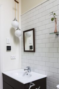 New tiled bathroom with our trademark double opal globes on textile lighting cable.